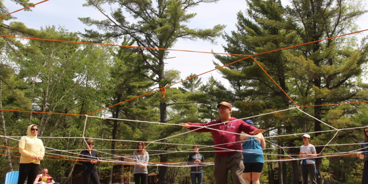Outdoor activity with women standing in a circle holding a circle of ropes tied together and a person standing in the center of the ropes.